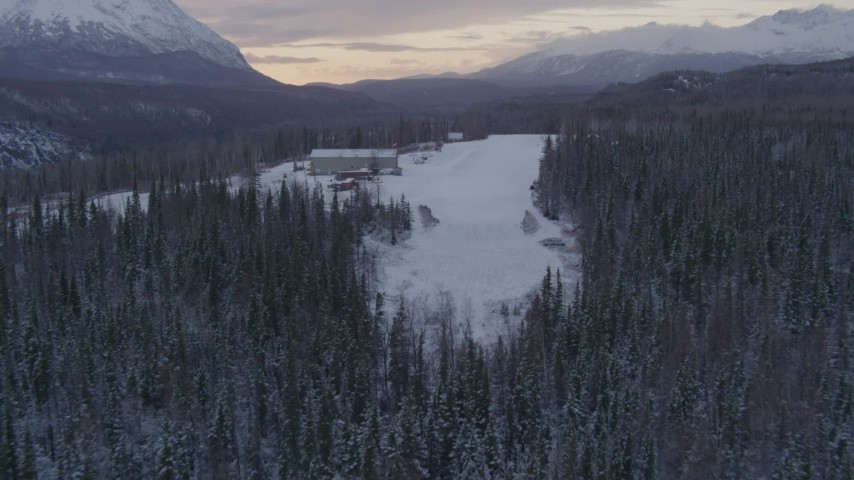 4K aerial video approach King Ranch, landing on snow near airplanes, Sutton, Alaska, twilight Aerial Stock Footage | AK0001_1104