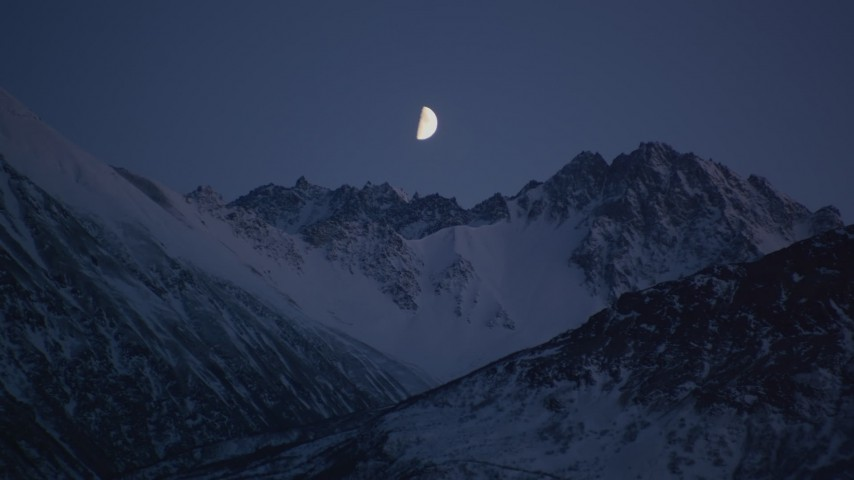 4K stock footage aerial video the moon over the snow covered Chugach Mountains at night, Alaska Aerial Stock Footage AK0001_1105 | Axiom Images