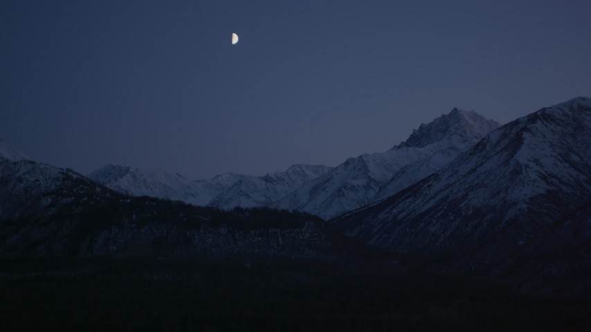 4K stock footage aerial video the moon over the snow covered Chugach Mountains at night, Alaska Aerial Stock Footage | AK0001_1108