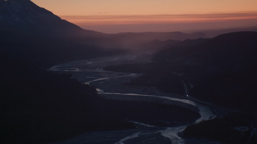 4K stock footage aerial video descending toward a highway and river in the snow covered Matanuska River Valley at sunset, Alaska Aerial Stock Footage   AK0001_1115