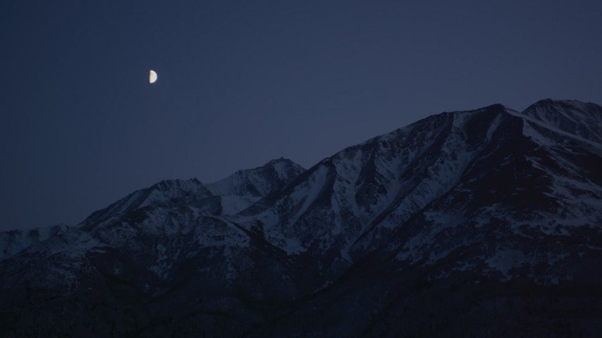 4K stock footage aerial video the moon over the snow covered Chugach Mountains at night, Alaska Aerial Stock Footage | AK0001_1117