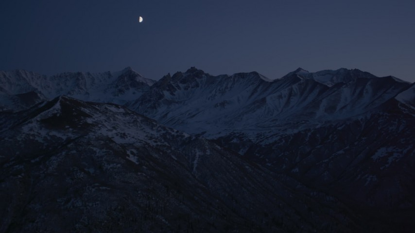 4K stock footage aerial video the moon over the snow covered Chugach Mountains at night, Alaska Aerial Stock Footage | AK0001_1121