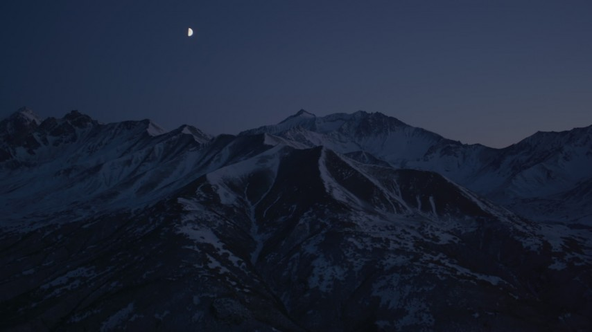 4K aerial video the moon over the snow covered Chugach Mountains at night, Alaska Aerial Stock Footage AK0001_1123