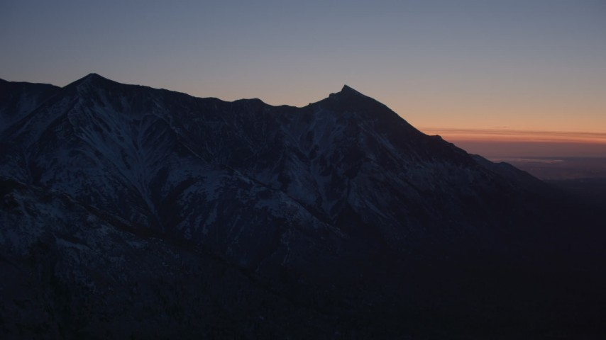 4K aerial video flying toward snow covered Chugach Mountains at twilight, Alaska Aerial Stock Footage | AK0001_1124