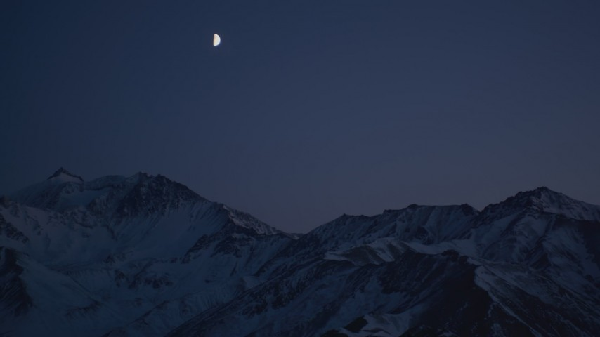 4K stock footage aerial video the moon over the snow covered Chugach Mountains at night, Alaska Aerial Stock Footage | AK0001_1126
