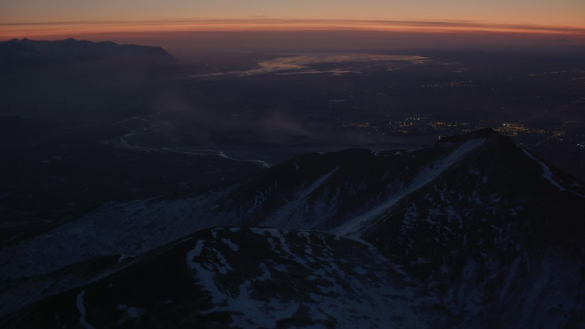 4K stock footage aerial video snow covered Chugach Mountains toward Knik River Valley, Alaska, twilight Aerial Stock Footage | AK0001_1137