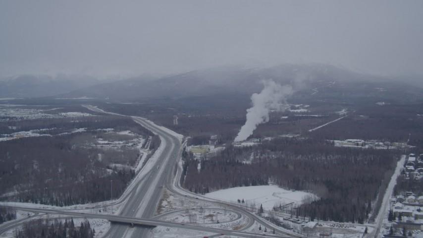 4K stock footage aerial video following Glenn Highway toward power plant in snow, Anchorage, Alaska Aerial Stock Footage | AK0001_1151