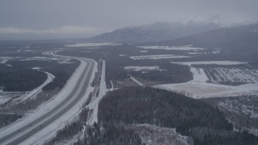 4K aerial video flying beside snow covered Glenn Highway, Fort Richardson, Anchorage, Alaska Aerial Stock Footage | AK0001_1155