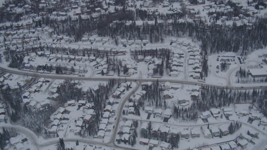 4K aerial video flying over snow covered neighborhoods and trees in Eagle River, Alaska Aerial Stock Footage | AK0001_1161