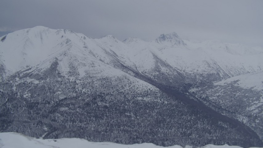 4K stock footage aerial video flying over snowy summit revealing wooded valley, Chugach Mountains, Alaska Aerial Stock Footage | AK0001_1174