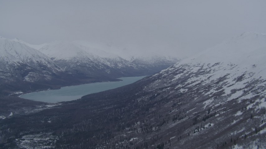 4K stock footage aerial video flying over snowy summit revealing Eklutna Lake and Chugach Mountains, Alaska Aerial Stock Footage | AK0001_1182