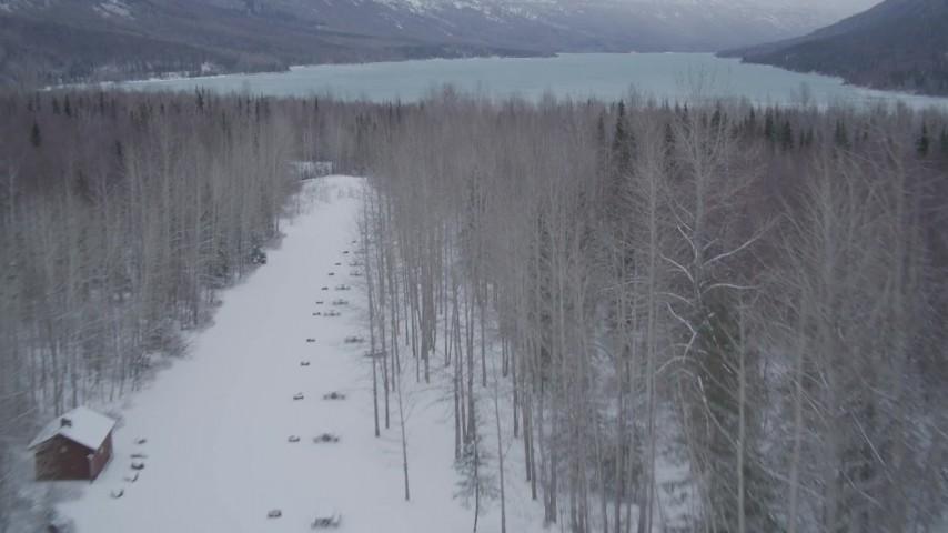 4K stock footage aerial video descending toward snow covered tree line, flying toward Eklutna Lake, Alaska Aerial Stock Footage | AK0001_1183