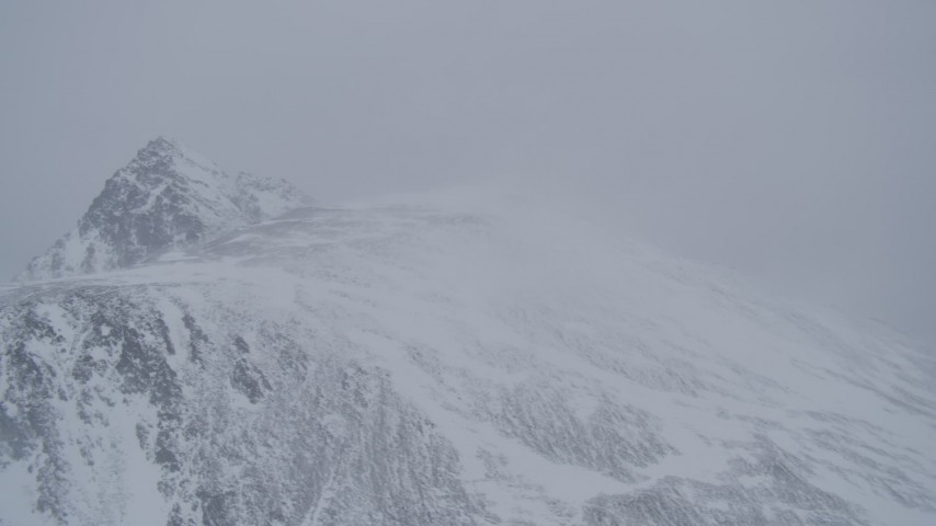 4K stock footage aerial video wind blowing snow off mountain ridge, Chugach Mountains, Alaska Aerial Stock Footage | AK0001_1208