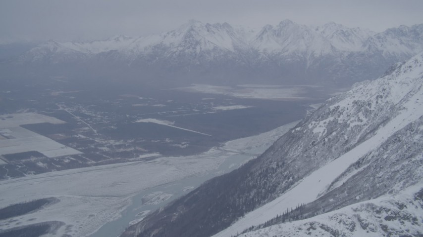 4K stock footage aerial video Butte and Knik River Valley at base of snow covered Chugach Mountains, Alaska Aerial Stock Footage | AK0001_1210
