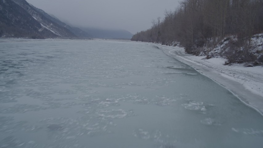 4K stock footage aerial video following the snowy, wooded riverbank of an icy river, Butte, Alaska Aerial Stock Footage | AK0001_1273