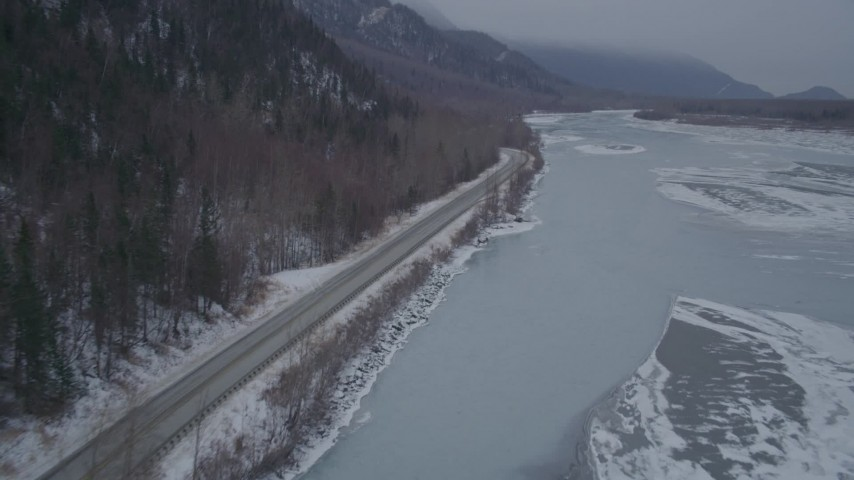 4K stock footage aerial video following Old Glenn Highway next to an icy river and snow, Butte, Alaska Aerial Stock Footage | AK0001_1278