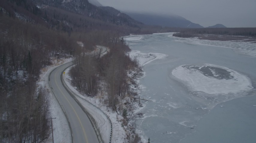 4K stock footage aerial video flying between Old Glenn Highway and icy river over snow, Butte, Alaska Aerial Stock Footage | AK0001_1279