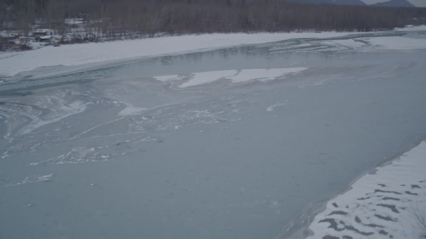 4K stock footage aerial video flying over snow covered trees revealing icy river, Butte, Alaska Aerial Stock Footage | AK0001_1280