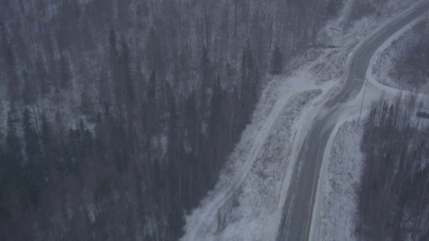 4K aerial video flying over forest to Glenn Highway through falling snow, Eagle River, Alaska Aerial Stock Footage | AK0001_1309