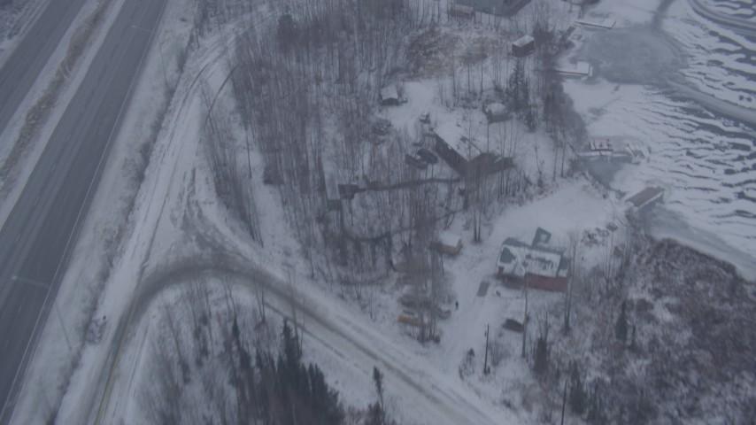 4K stock footage aerial video flying over frozen lake, snowy houses, reveal Glenn Highway, Eagle River, Alaska Aerial Stock Footage | AK0001_1310