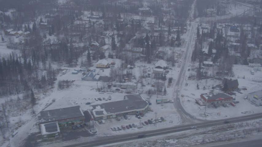 4K aerial video flying by neighborhoods, reveal Glenn Highway, falling snow, Eagle River, Alaska Aerial Stock Footage | AK0001_1311