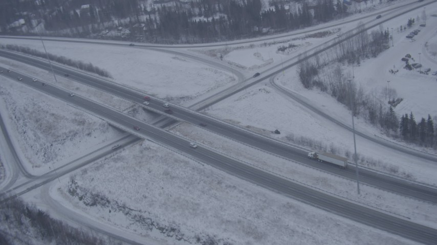 4K aerial video orbiting a Glenn Highway overpass in falling snow, Eagle River, Alaska Aerial Stock Footage | AK0001_1312