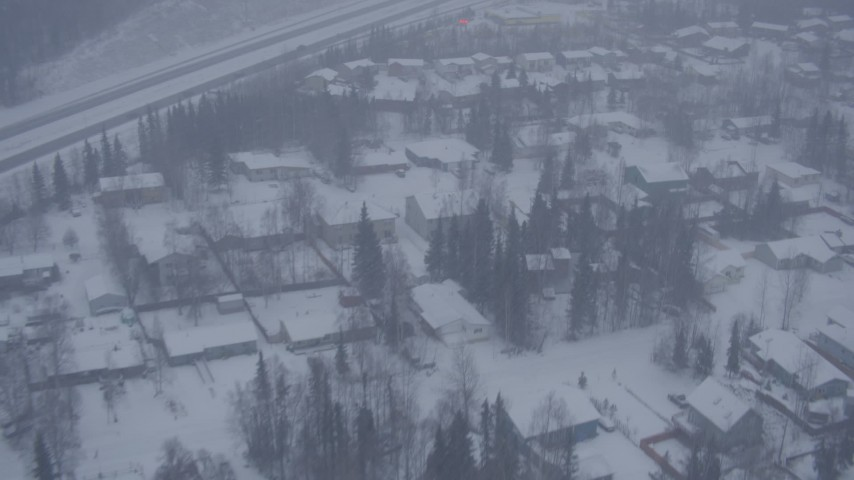 4K stock footage aerial video flying over neighborhoods near Glenn Highway in falling snow, Eagle River, Alaska Aerial Stock Footage AK0001_1315 | Axiom Images