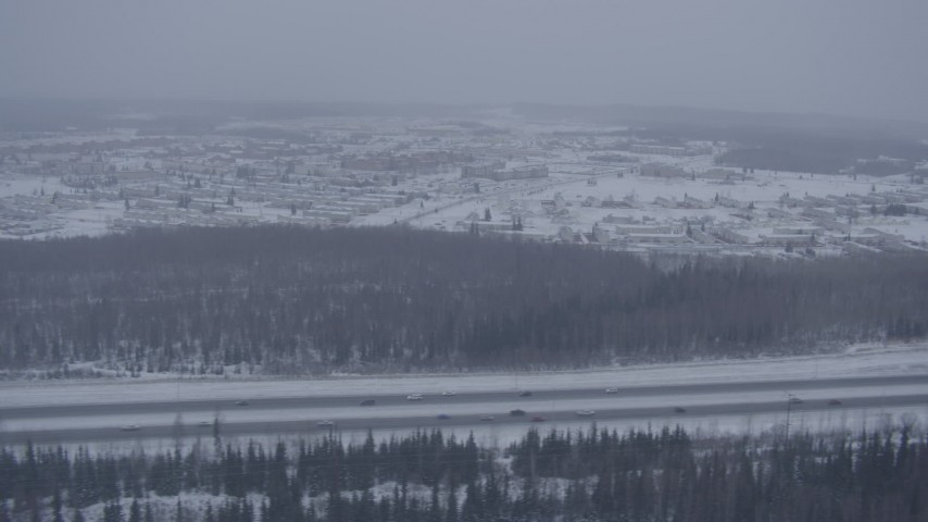 4K aerial video tracking cars on Glenn Highway in falling snow, Fort Richardson, Anchorage, Alaska Aerial Stock Footage AK0001_1320