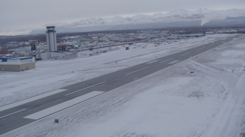 4K stock footage aerial video pan across snowy Merrill Field toward Chugach Mountains, Anchorage, Alaska Aerial Stock Footage   AK0001_1327