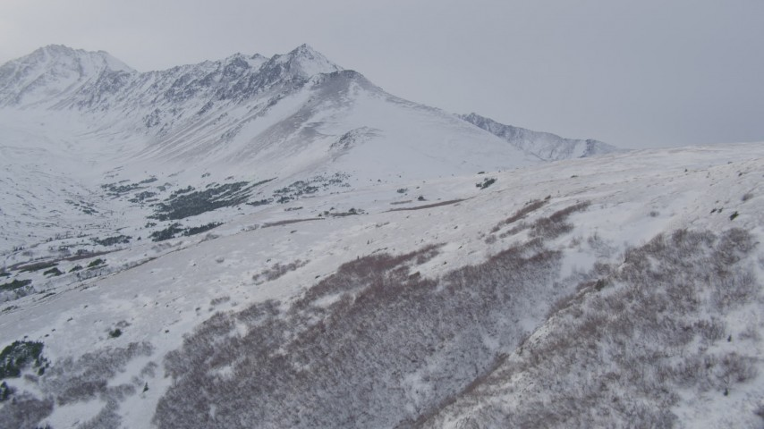 4K stock footage aerial video flying up a snow covered slope revealing peaks in the Chugach Mountains, Alaska Aerial Stock Footage | AK0001_1336