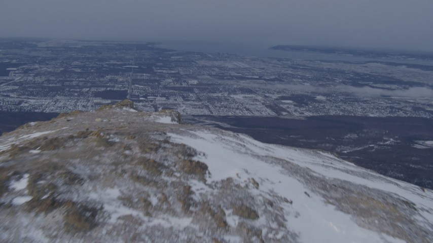 4K stock footage aerial video flying over a snow covered mountain peak revealing Anchorage, Alaska Aerial Stock Footage | AK0001_1338