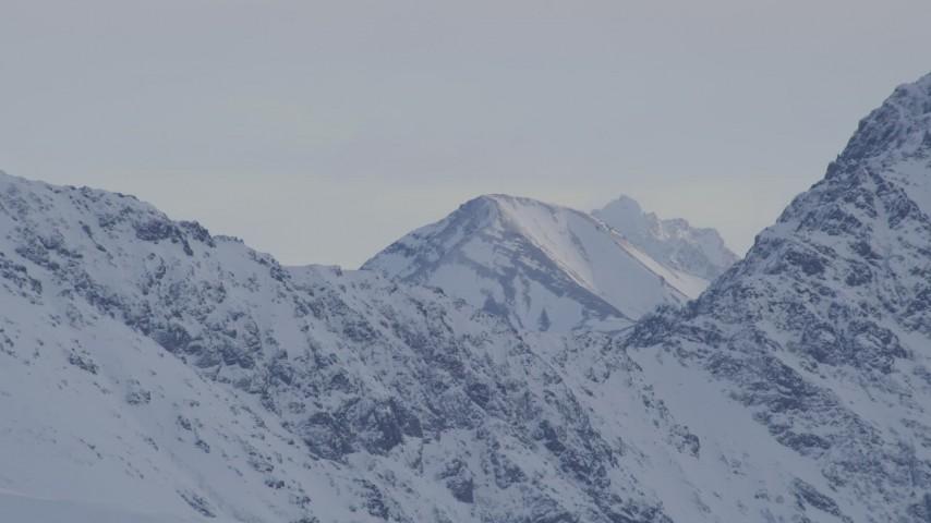 4K stock footage aerial video a peak seen over a snowy ridge, Chugach Mountains, Alaska Aerial Stock Footage | AK0001_1348