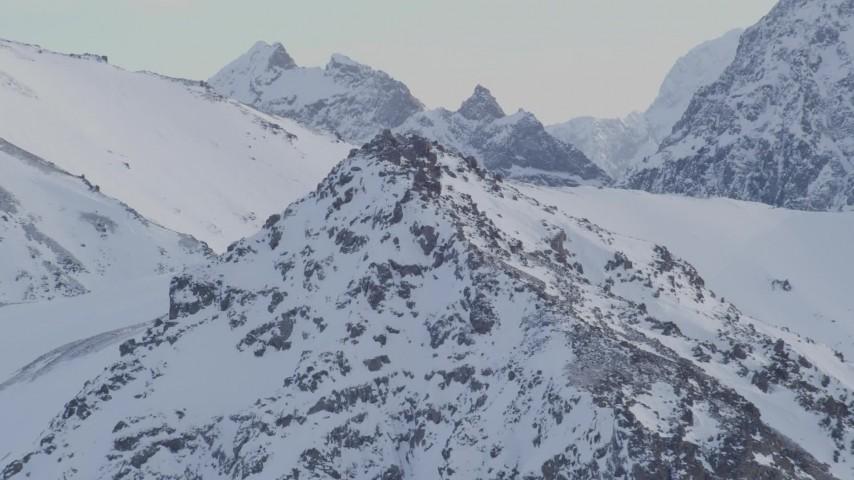 4K stock footage aerial video flying over a rocky peak toward a snowy summit in Chugach Mountains, Alaska Aerial Stock Footage | AK0001_1351
