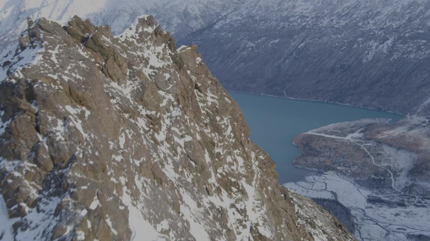 4K stock footage aerial video flying over a rocky, snow covered peak revealing Eklutna Lake, Alaska Aerial Stock Footage | AK0001_1353