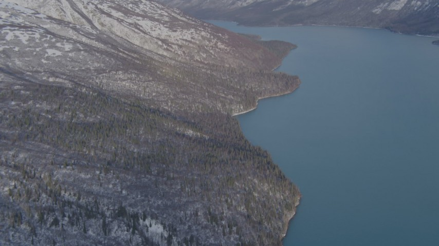 4K stock footage aerial video approaching snow covered mountain slopes along shore of Eklutna Lake, Alaska Aerial Stock Footage | AK0001_1355