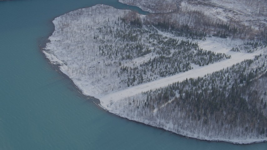 4K stock footage aerial video orbiting snow covered, wooded shore of Eklutna Lake, Alaska Aerial Stock Footage AK0001_1356 | Axiom Images