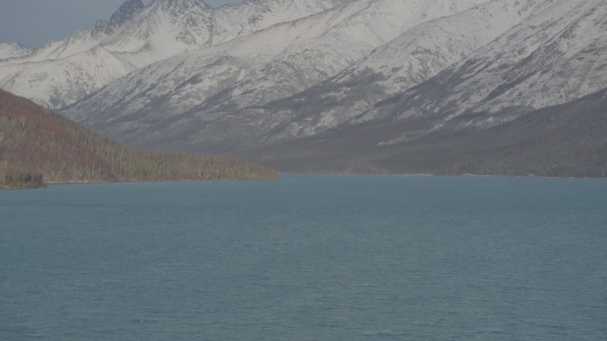 4K stock footage aerial video surface of Eklutna Lake, snow covered, wooded hills, Chugach Mountains, Alaska Aerial Stock Footage | AK0001_1360