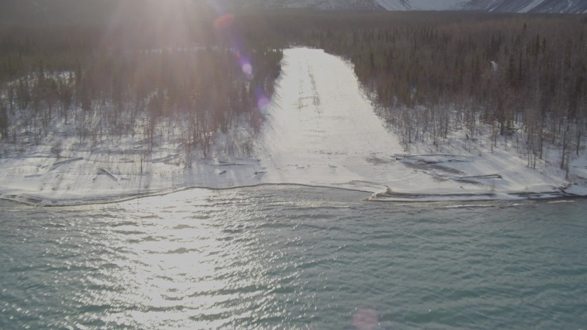 4K stock footage aerial video flying over Eklutna Lake, descending toward snowy strip in woods, Alaska Aerial Stock Footage | AK0001_1361