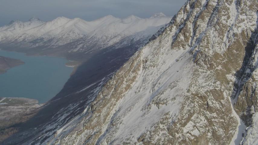 4K stock footage aerial video flying toward rocky, snowy slope near Eklutna Lake, Alaska Aerial Stock Footage | AK0001_1367