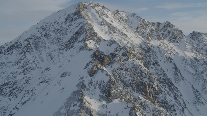 Approach and fly over a rocky, snow covered mountain peak, Chugach Mountains, Alaska Aerial Stock Footage | AK0001_1374