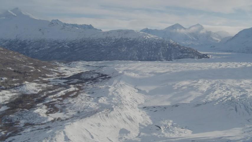 4K aerial video flying along edge of snow covered Knik Glacier toward Chugach Mountains, Alaska Aerial Stock Footage | AK0001_1388