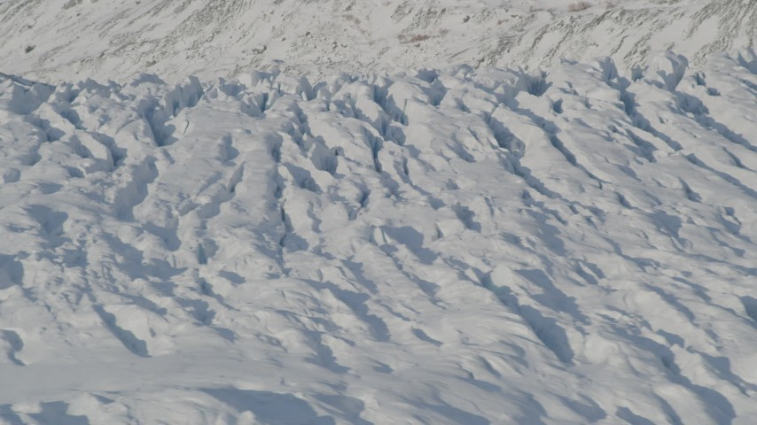 4K aerial video the cracked, snow covered surface of the Knik Glacier, Alaska Aerial Stock Footage | AK0001_1406