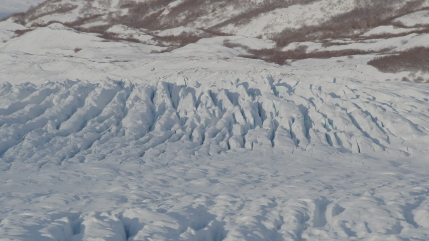 4K aerial video flying past cracked, snow covered surface of Knik Glacier, Alaska Aerial Stock Footage | AK0001_1407