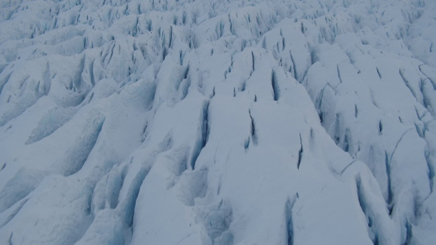4K aerial video the surface of the cracked, snow covered Knik Glacier, Alaska Aerial Stock Footage | AK0001_1410