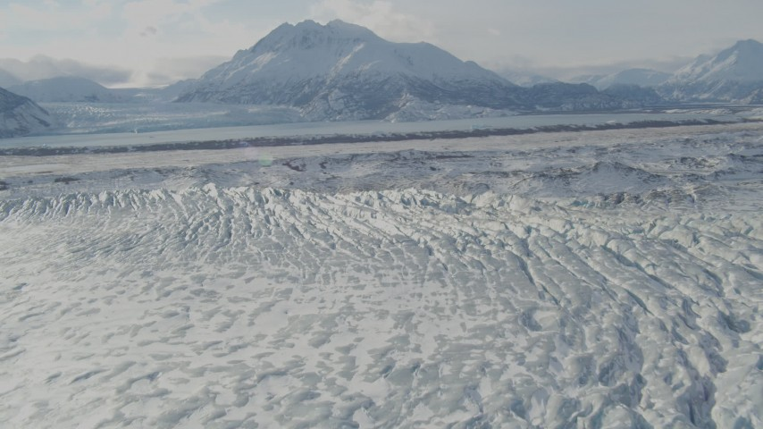 4K aerial video flying over snow covered Knik Glacier, Chugach Mountains in distance, Alaska Aerial Stock Footage AK0001_1430