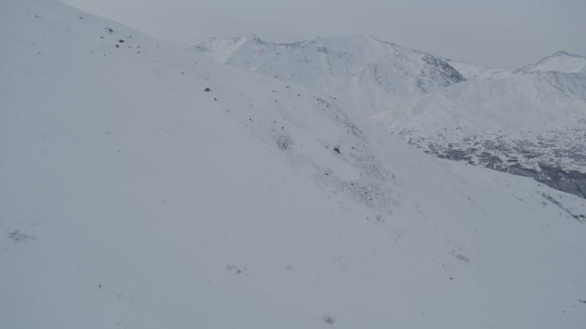 4K stock footage aerial video flying over snowy slope toward mountain range, Chugach Mountains, Alaska Aerial Stock Footage | AK0001_1487