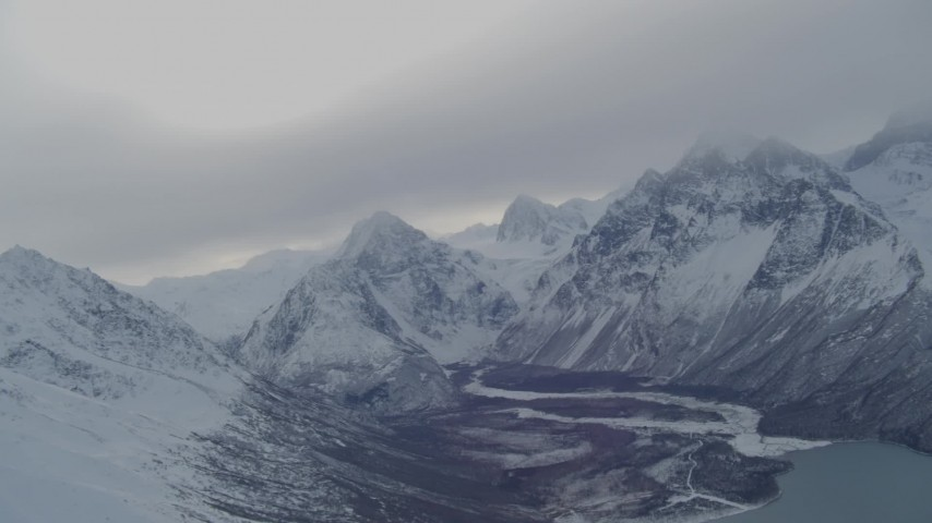 4K stock footage aerial video panning across snow covered Chugach Mountains revealing Eklutna Lake, Alaska Aerial Stock Footage | AK0001_1494