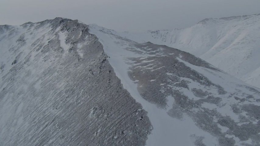 4K stock footage aerial video flying toward and over a snow covered slope in the Chugach Mountains, Alaska Aerial Stock Footage | AK0001_1498