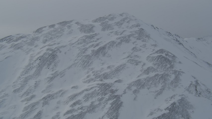 4K stock footage aerial video flying up and over a snow covered mountain slope, Chugach Mountains, Alaska Aerial Stock Footage | AK0001_1499