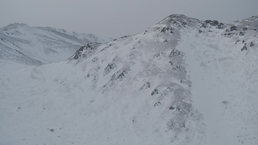 4K stock footage aerial video flying over summit of snow covered mountain, Chugach Mountains, Alaska Aerial Stock Footage | AK0001_1506
